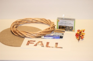 Supplies to make a DIY fall wreath. Wooden wreath, canvas circles, cooper wire lights, batteries, stem decoration, fall letters and glue on a white background.