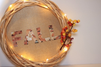 Finished DIY fall wreath made out of wooden wreath, copper wire lights, stem decoration, and fall letters.
