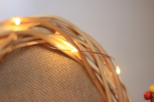 Copper wire lights wrapped into a wooden wreath.