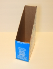 Tall cardboard cereal box with top half in a triangle shape cut out.