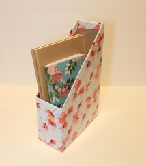 Finished DIY magazine holder made from cardboard box and wrapping paper and holding notebooks.