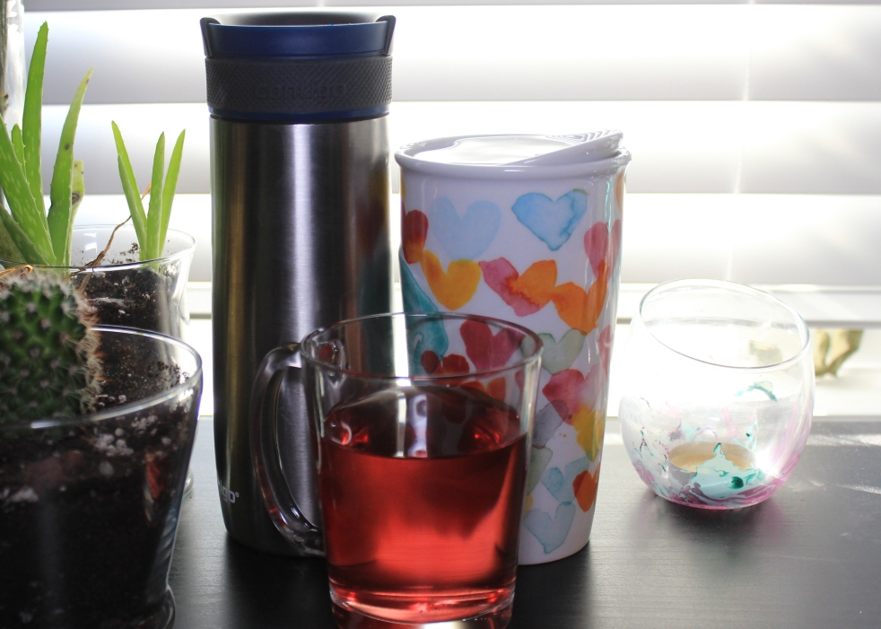 Contigo take-out mug, Starbucks mug with hearts and a clear glass mug with blueberry tea on a desk.