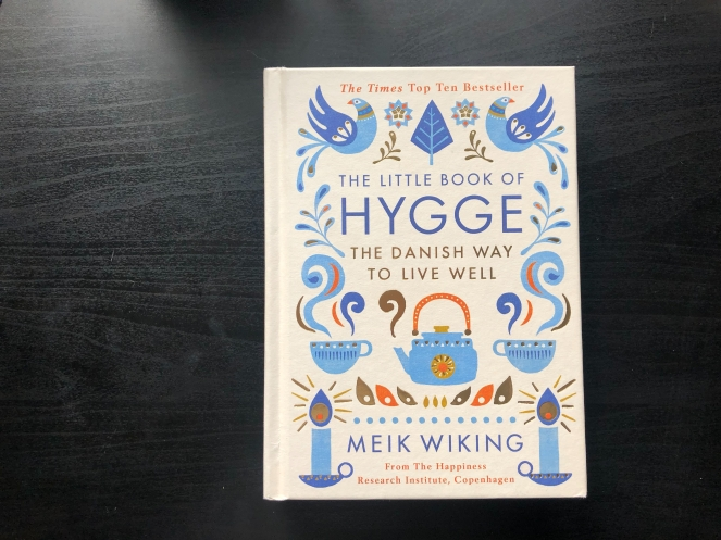 The Little Book of Hygge The Danish Way to Live Well by Meik Wiking on a dark wood table