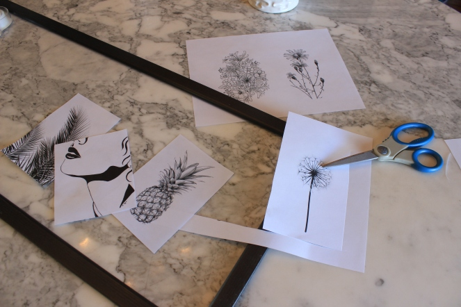 Black frame and black and white illustrations being cut out on a marble table